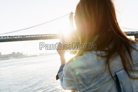 young woman photographing manhattan bridge with
