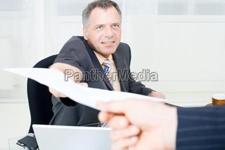businessman handing over a piece of