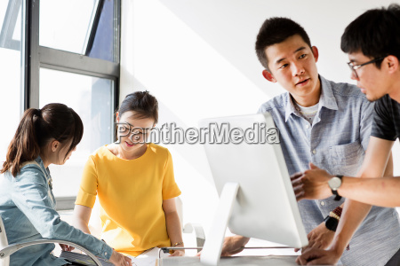 young adults sitting around computer