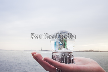 young womans hand holding landmark snowglobe