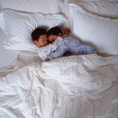 two young boys cuddled in bed