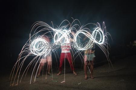 four adult friends making sparkler patterns