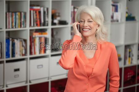 mature woman using mobile phone indoors