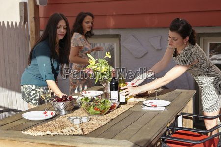 three female friends preparing lunch on