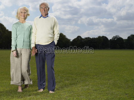 elderly couple holding hands in park