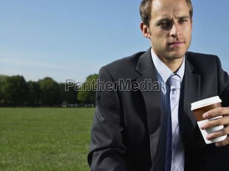 serious looking businessman in a park