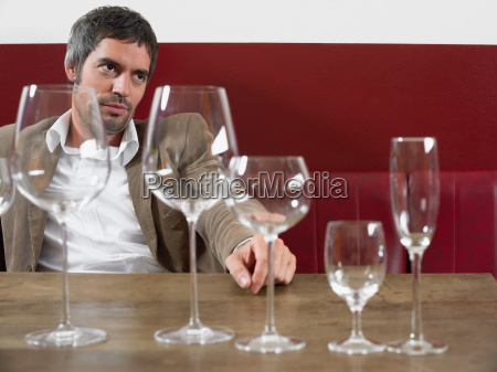 man sitting at table with wine
