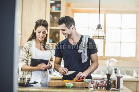couple preparing food and using digital