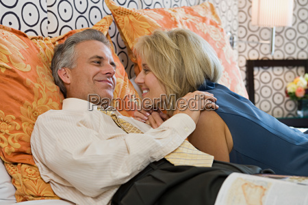 mature couple lying on bed