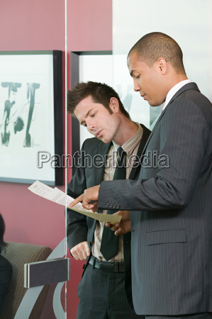 two businessmen looking at paperwork