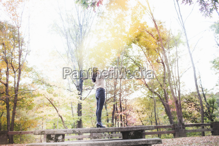 young woman standing on picnic bench