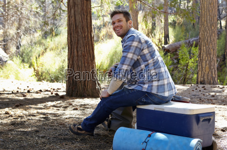 young man in forest sitting on