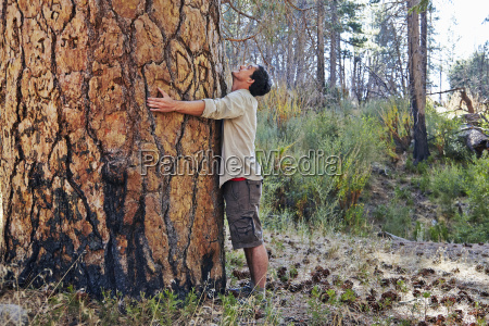 young man in forest hugging large