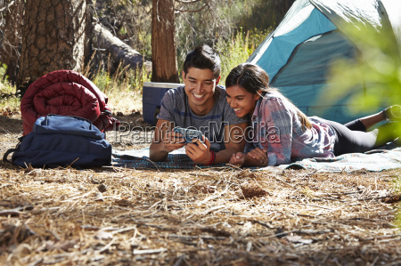 young camping couple looking at smartphone
