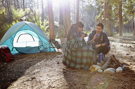 young camping couple drinking coffee in