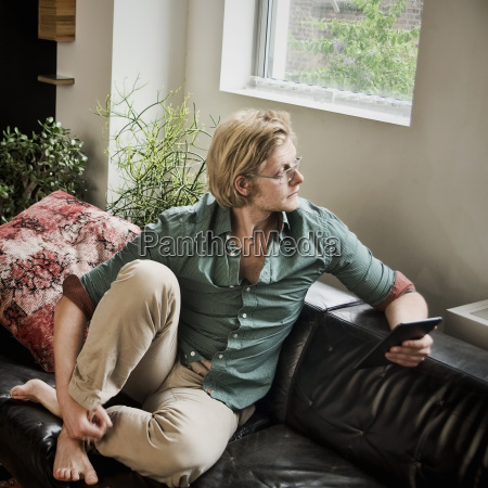 young man sitting on sofa with
