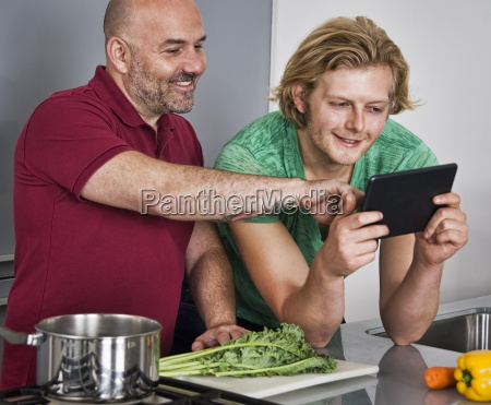 male couple using digital tablet whilst
