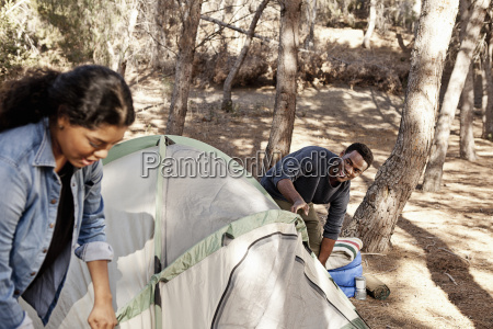 young couple putting up tent in