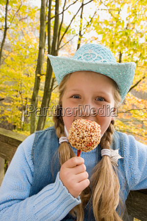 girl eating a toffee apple