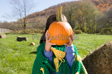 girl holding pumpkin in front of
