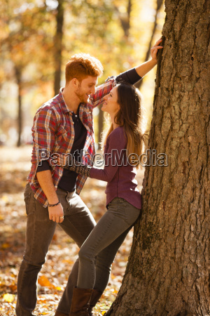 romantic young couple leaning against tree