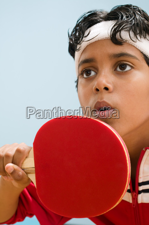 boy holding table tennis paddle