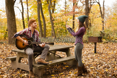 young woman photographing guitar playing boyfriend