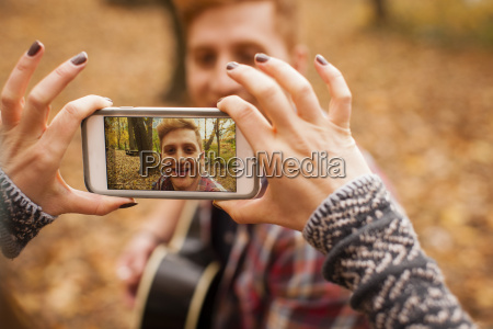 hands of young woman photographing boyfriend