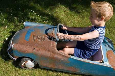 boy in an old toy car