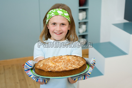 girl holding an almond cake