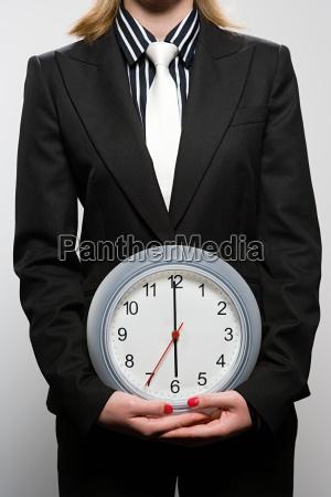businesswoman holding a clock