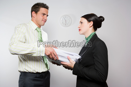businessman handing colleague paperwork