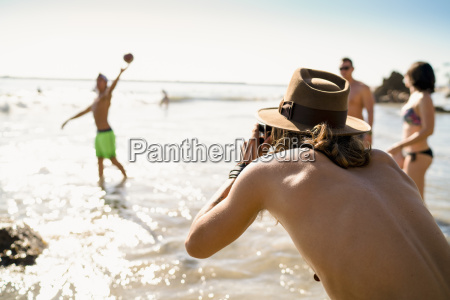 young man photographing friends playing