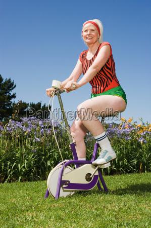senior adult woman riding an exercise