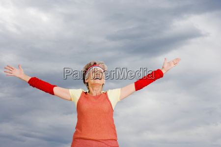 senior adult woman with arms up
