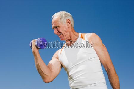 senior adult man lifting a dumbbell