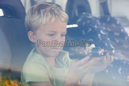 boy sat in car holding toy