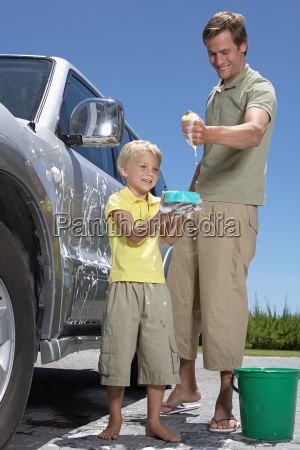father and son washing family car