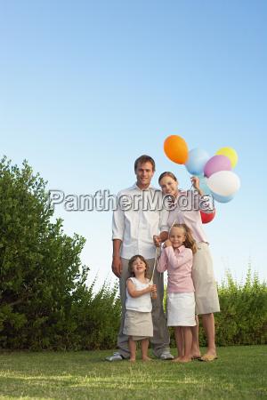 portrait of family stood in garden