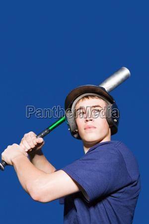 teenage boy about to swing baseball