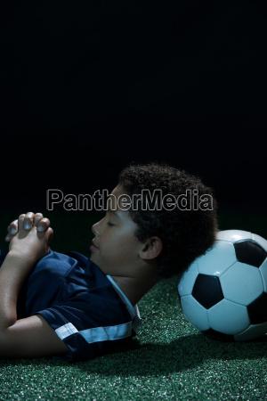 boy sleeping with football as pillow