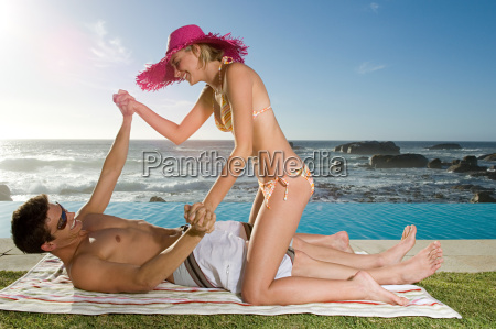 couple playfighting by pool