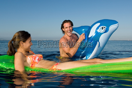 couple in the sea with inflatables