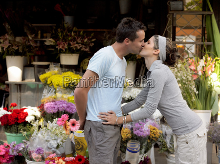 couple kissing by flower stall