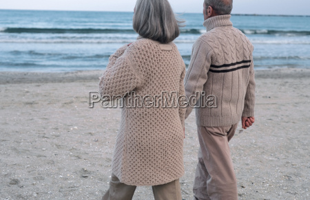 senior couple walking near sea