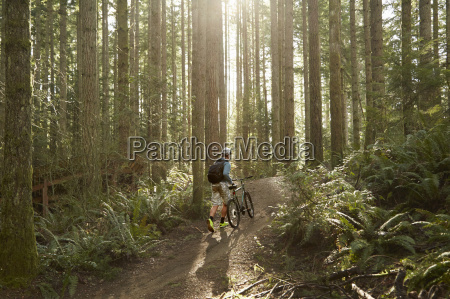 young man walking mountain bike through