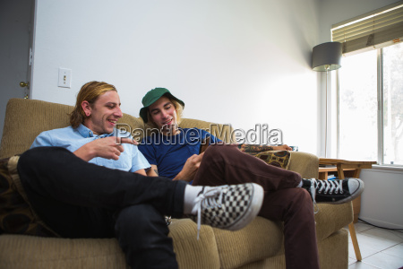 two young men sitting on sofa