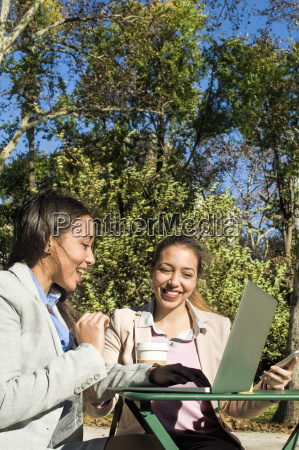 young adult female twins typing on