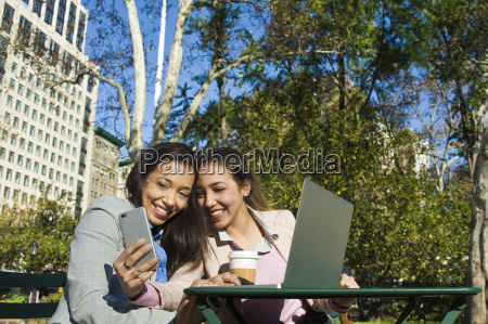 young adult female twins taking smartphone