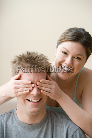 woman covering husbands eyes